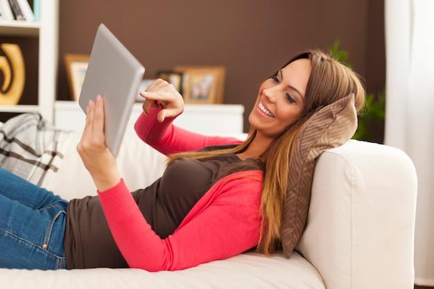 Lächelnde frau, die auf sofa liegend und digitales tablett benutzt