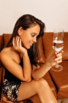 Lächelnde frau, die auf sofa mit hellem make-up und welligem haar sitzt und ein glas wein hält