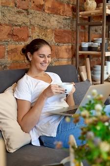 Lächelnde frau, die auf sofa sitzt, laptop betrachtet und tee trinkt
