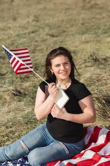 Lächelnde frau, die auf streifenfahne sitzt und amerikanische flagge hält