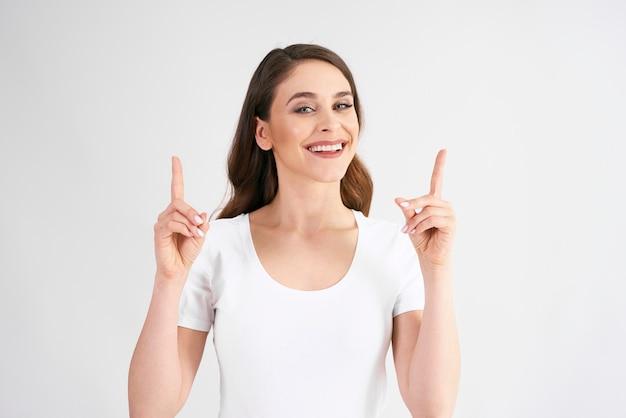 Lächelnde frau, die auf textfreiraum zeigt