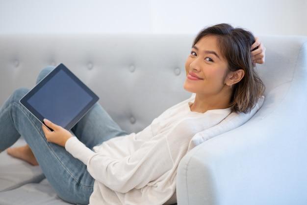 Lächelnde frau, die auf trainer mit pc-tablette und rührendem haar liegt