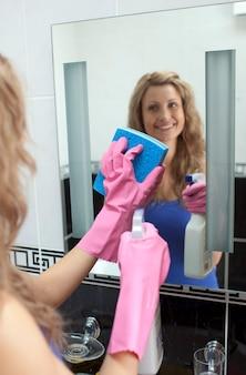 Lächelnde frau, die badezimmerspiegel reinigt