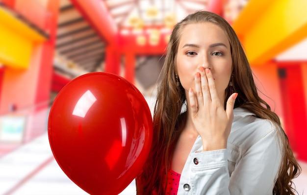 Lächelnde frau, die ballon hält und kuss sendet