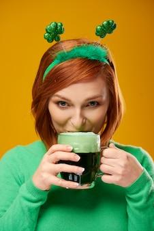 Lächelnde frau, die bier trinkt