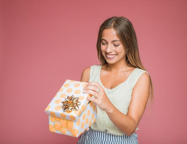 Lächelnde frau, die blumengeschenkbox mit goldenem bogen gegen farbigen hintergrund öffnet