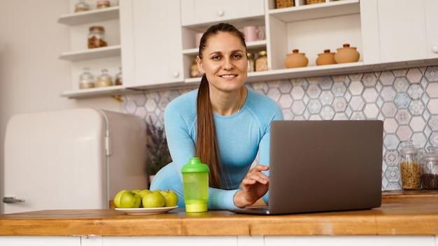 Lächelnde frau, die computer im modernen kücheninnenraum benutzt. konzept des kochens und des gesunden lebensstils. eine frau schaut in die kamera und lächelt