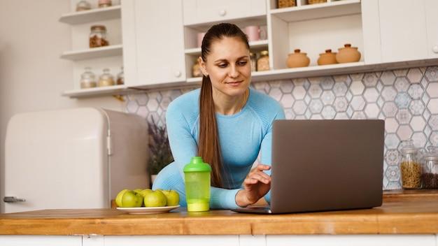 Lächelnde frau, die computer im modernen kücheninnenraum benutzt. konzept des kochens und des gesunden lebensstils. eine frau sucht nach einem rezept oder streamt online