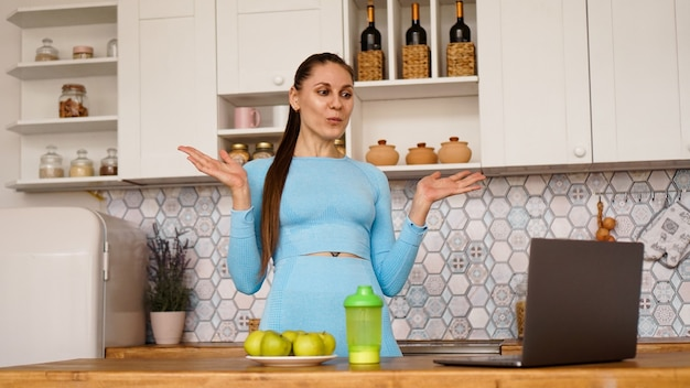 Lächelnde frau, die computer im modernen kücheninnenraum benutzt. konzept des kochens und des gesunden lebensstils. frau sendet online und gestikuliert emotional