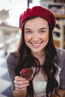 Lächelnde frau, die cupcake hält