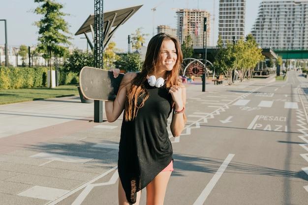 Lächelnde frau, die das skateboard steht auf straße hält