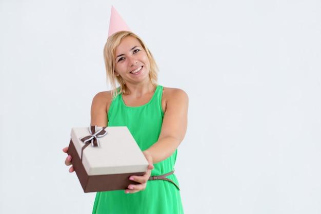 Lächelnde frau, die dem zuschauer geschenkbox gibt