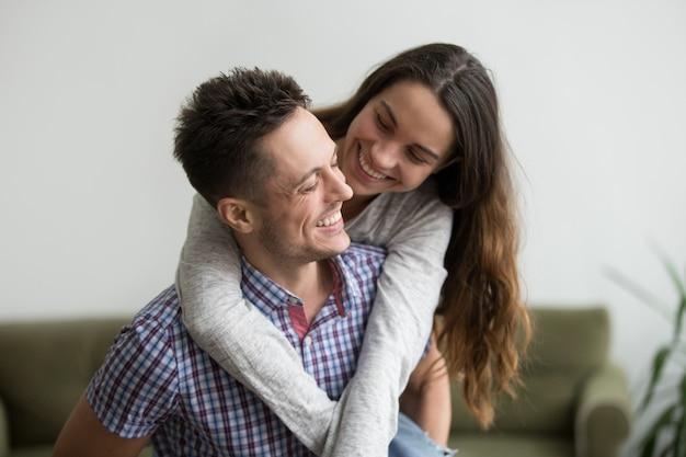 Lächelnde frau, die den jungen ehemann umarmt, der sie zu hause huckepack trägt