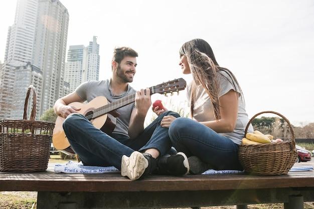 Lächelnde frau, die den mann spielt gitarre picknick betrachtet