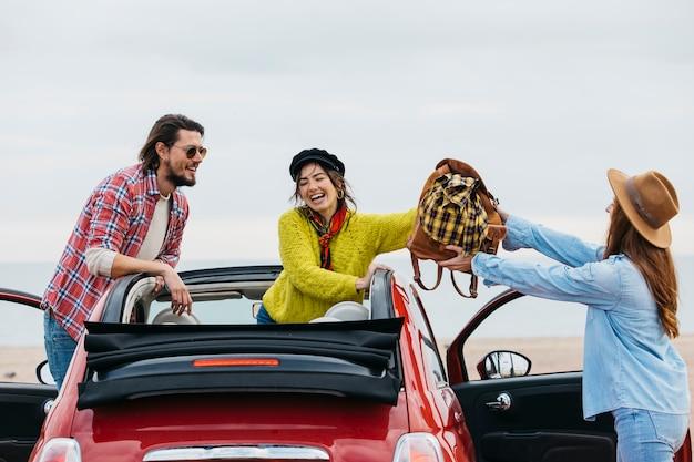 Lächelnde frau, die der dame nahe mann rucksack heraus lehnt vom auto gibt