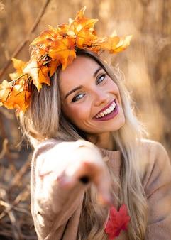 Lächelnde frau, die die trockene ahornblatttiara zeigt in richtung zur kamera trägt