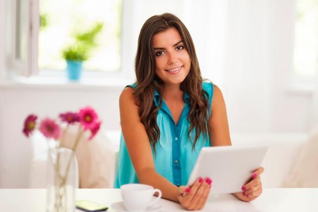 Lächelnde frau, die digitales tablett zu hause verwendet