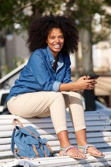 Lächelnde frau, die draußen auf bank mit handy sitzt