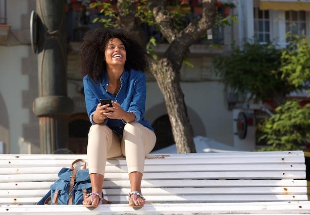 Lächelnde frau, die draußen auf bank mit intelligentem telefon sitzt