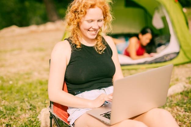 Lächelnde frau, die draußen auf laptop plaudert