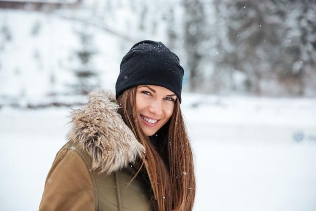 Lächelnde frau, die draußen mit schnee in die kamera schaut