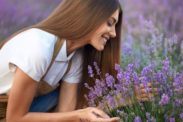Lächelnde frau, die duft im lavendelfeld riecht
