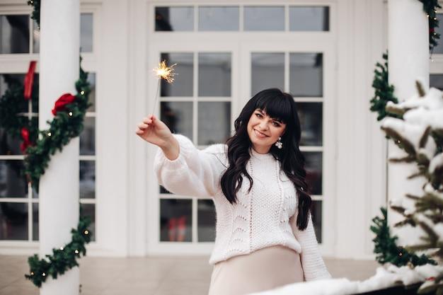 Lächelnde frau, die ein bengalisches licht hält, während draußen vor einem weißen haus steht.