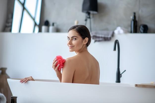 Lächelnde frau, die ein entspannendes bad mit einem schwamm nimmt