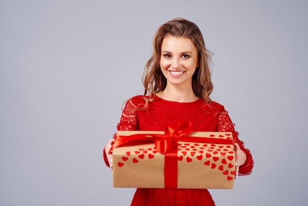 Lächelnde frau, die ein geschenk macht