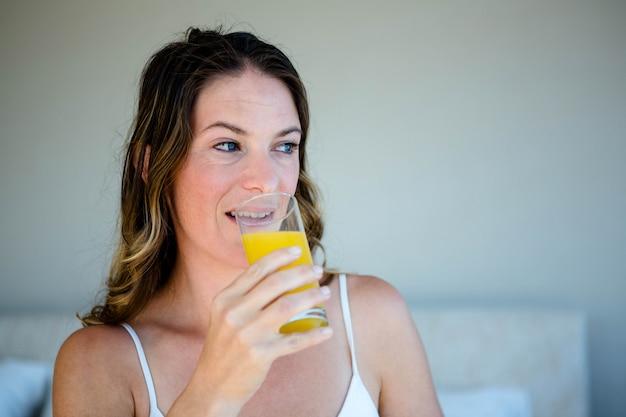 Lächelnde frau, die ein glas orangensaft in ihrem schlafzimmer nippt