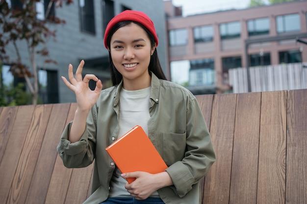 Lächelnde frau, die ein gutes zeichen zeigt, das kameraporträt des glücklichen asiatischen studenten anschaut, der buch hält