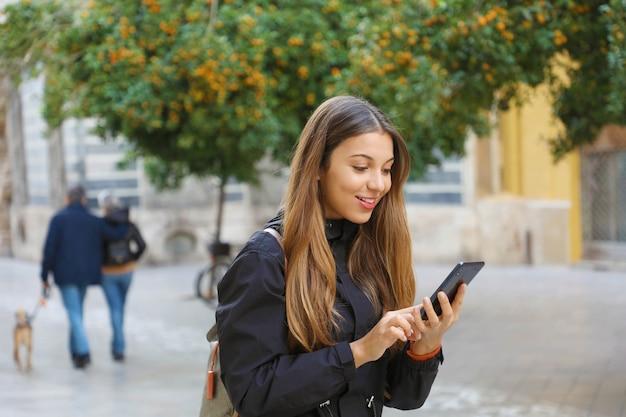 Lächelnde frau, die ein mobiltelefon in der stadtstraße mit mandarinenbäumen verwendet