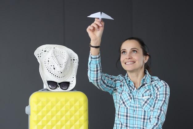 Lächelnde frau, die ein papierflugzeug neben koffer hält. um die welt reisen konzept