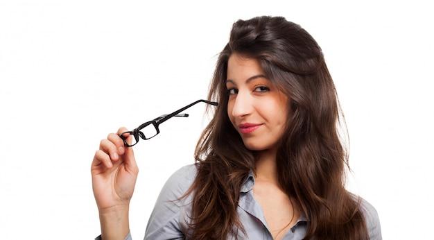 Lächelnde frau, die eine brille hält