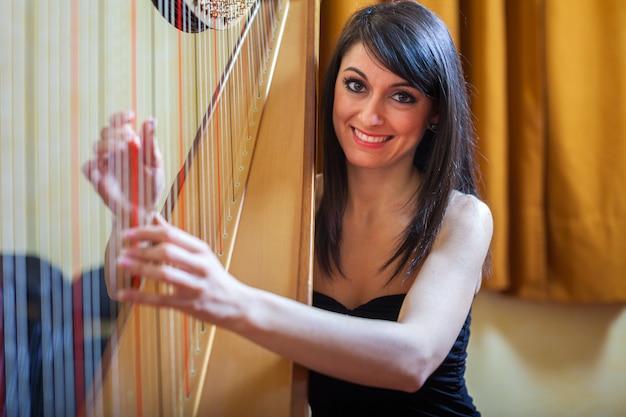 Lächelnde frau, die eine harfe spielt