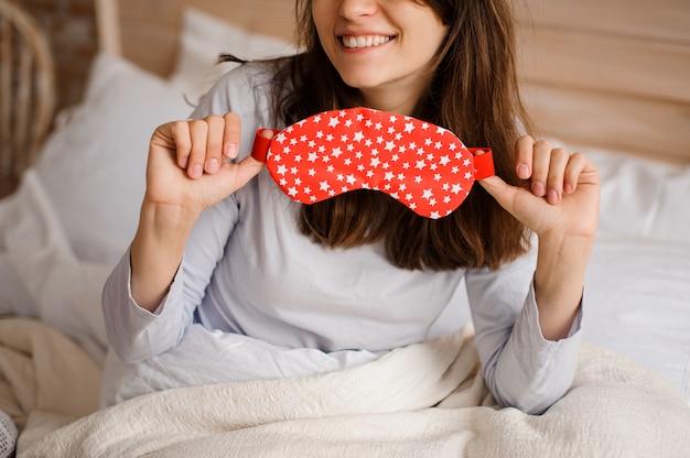 Lächelnde frau, die eine nette rote schlafmaske mit einem muster von kleinen sternen hält