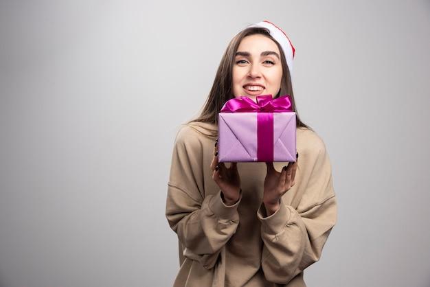 Lächelnde frau, die eine schachtel weihnachtsgeschenk hält.