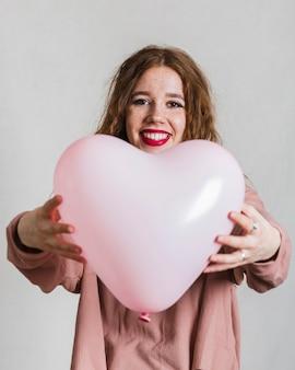 Lächelnde frau, die einen ballon anbietet