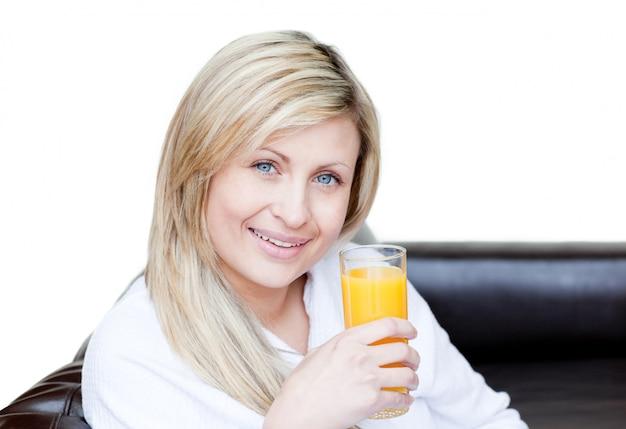 Lächelnde frau, die einen orange jus trinkt
