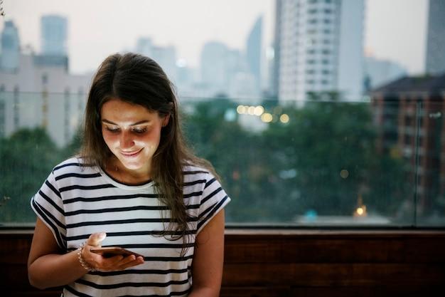 Lächelnde frau, die einen smartphone im stadtbild verwendet