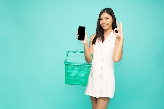 Lächelnde frau, die einkaufskorb und ok zeichen und handy hält