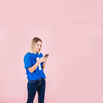 Lächelnde frau, die facebook-t-shirt unter verwendung des handys trägt