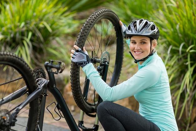Lächelnde frau, die fahrradreifen repariert