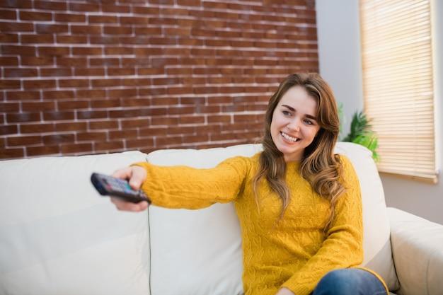 Lächelnde frau, die fernbedienung auf couch im wohnzimmer hält