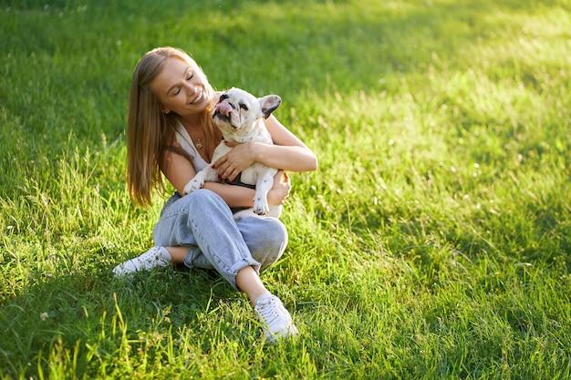 Lächelnde frau, die französische bulldogge auf gras umarmt