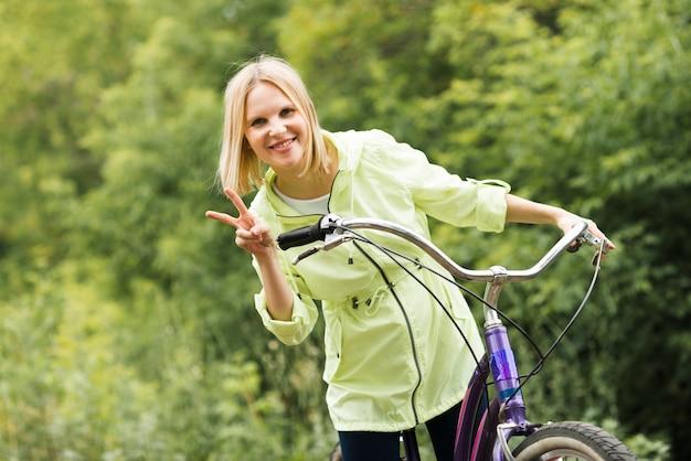 Lächelnde frau, die friedenszeichen auf fahrrad hält