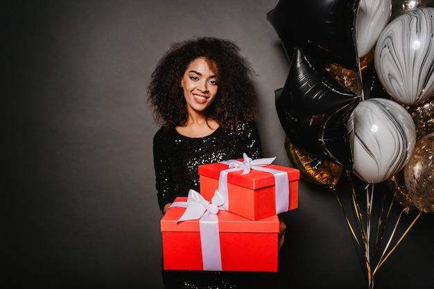 Lächelnde frau, die geburtstagsgeschenk hält