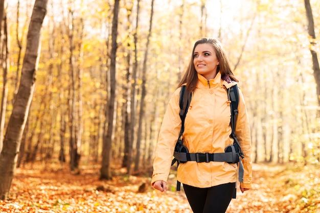 Lächelnde frau, die gelbe jacke trägt, die im wald geht