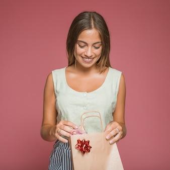 Lächelnde frau, die geschenkbox von der einkaufstasche mit rotem bogen entfernt
