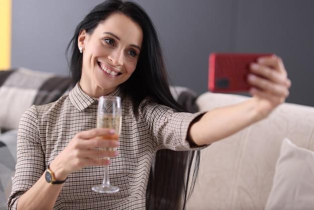 Lächelnde frau, die glas champagner hält und smartphonebildschirm betrachtet. feiern von veranstaltungen über das internet-online-konzept